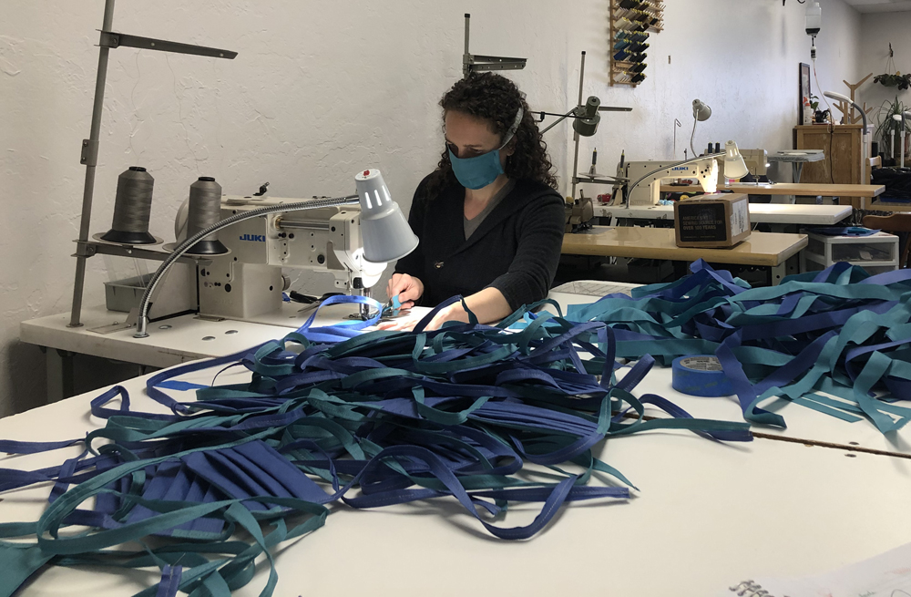 Me binding straps onto a big pile of face masks.