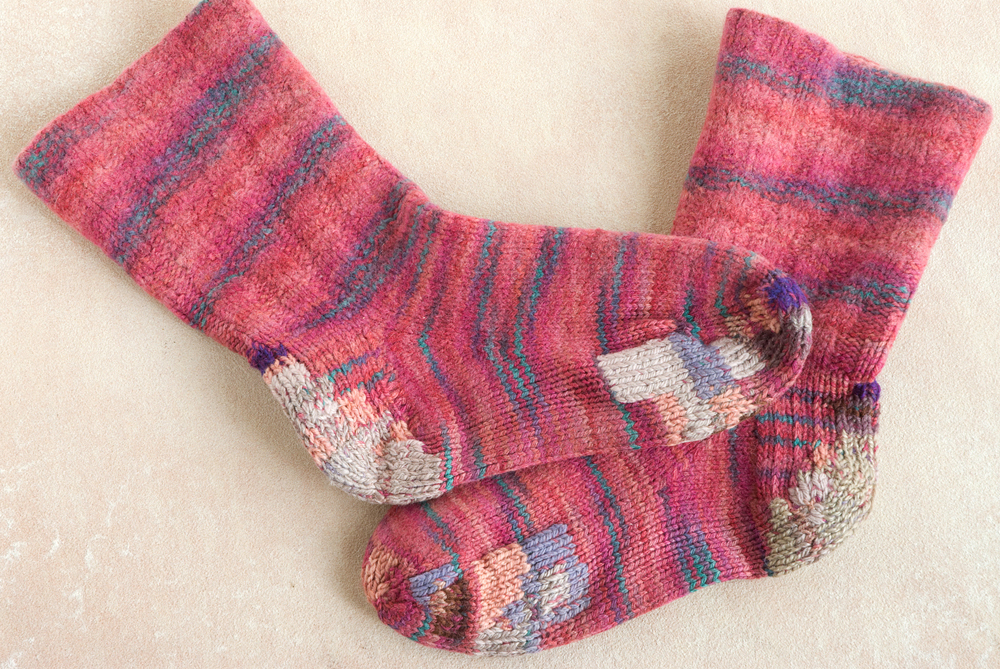 Fuchsia hand-knit socks with many overlapping duplicate-stitch patches in different yarns.