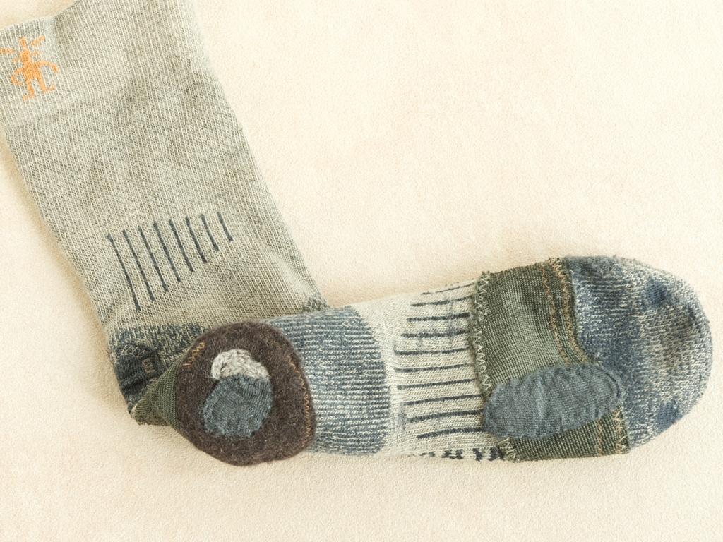Commercial wool sock with layers of patches and stitching.